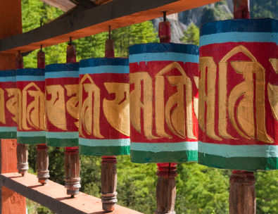 Bhutan row of traditional colorful painted prayer wheels